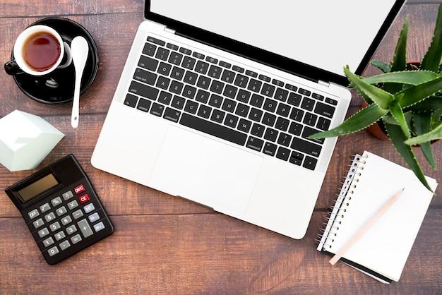 Un laptop aperto con tazza di caffè; quaderno a spirale; calcolatrice; modello di casa di carta e piante di aloe vera sul tavolo di legno