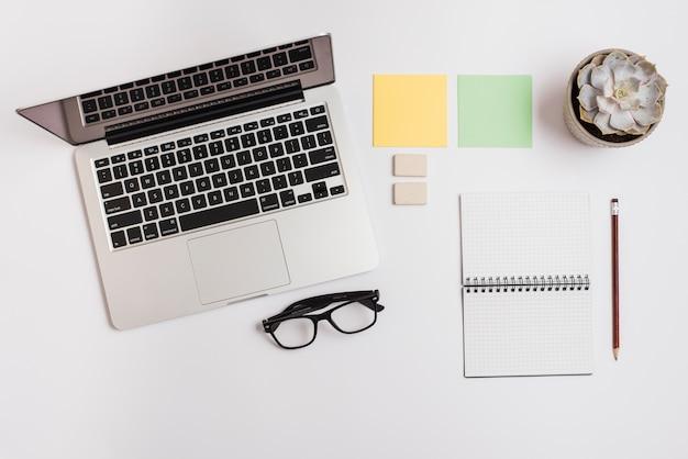 Un laptop aperto; nota adesiva; pianta di cactus; blocco note a spirale; matita e occhiali su sfondo bianco