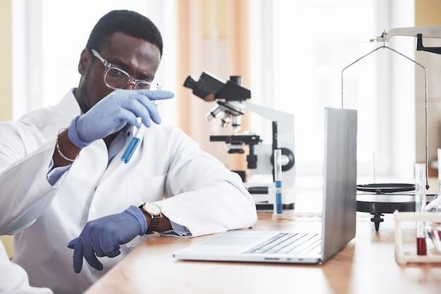 Un lavoratore afroamericano lavora in un laboratorio conducendo esperimenti.