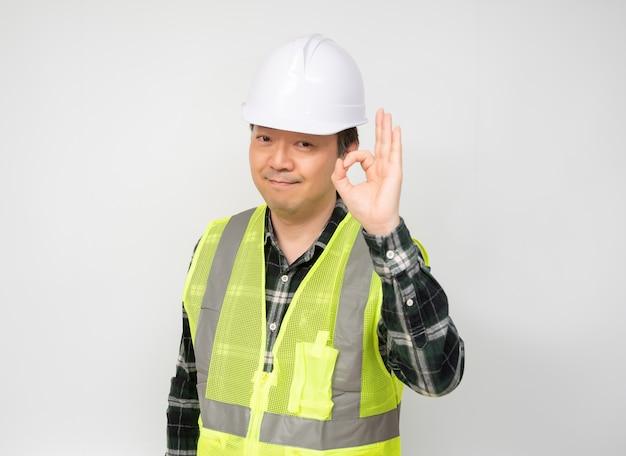 Un lavoratore asiatico di mezza età alza la mano e firma ok.