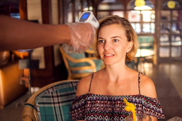 Un lavoratore che misura la temperatura della donna visitior all'interno del caffè. vita durante il tempo di coronavirus