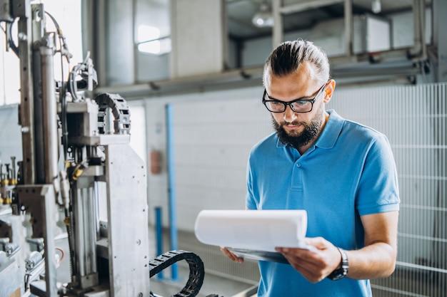 Un lavoratore con gli occhiali in piedi vicino ad attrezzature industriali e verifica i dati di produzione. uomo che tiene la cartella nelle mani
