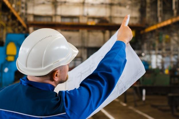 Un lavoratore in tuta e un elmetto bianco esamina il disegno e indica con il dito indice