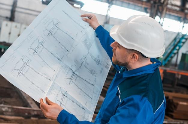 Un lavoratore in tuta e un elmetto bianco esamina il disegno