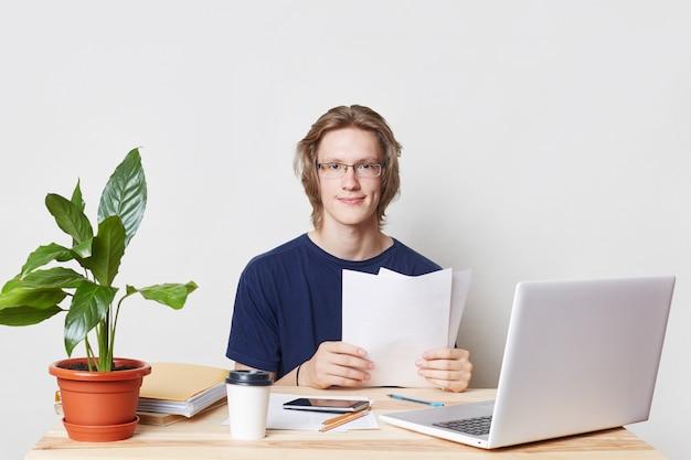 Un lavoratore professionale che lavora sodo si siede sul posto di lavoro, rivede i suoi conti, studia documenti, con espressione deliziosa, utilizza le moderne tecnologie per il lavoro