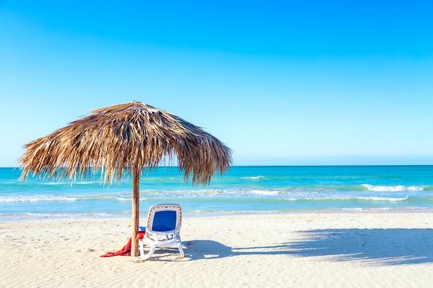 Un lettino sotto l'ombrellone sulla spiaggia di sabbia in riva al mare e al cielo.