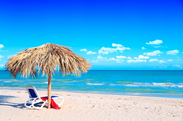 Un lettino sotto un ombrellone sulla spiaggia di sabbia in riva al mare e cielo nuvoloso.