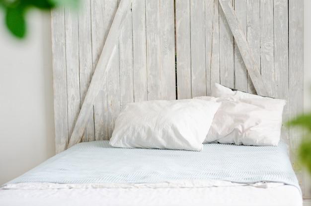 Un letto piccolo e accogliente con biancheria bianca e velo blu in una stanza con interni minimalisti scandinavi