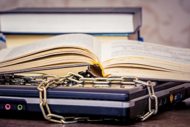 Un libro aperto giace su un laptop collegato da una catena
