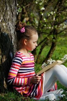 Un libro di lettura bella ragazza, seduto nel parco thr, sotto l'albero