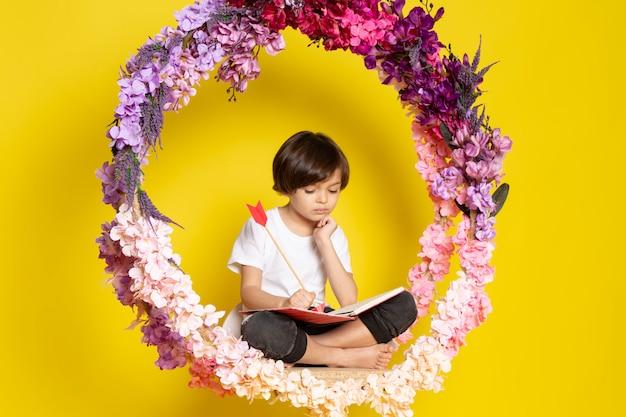 Un libro di lettura del ragazzo di vista frontale in maglietta bianca che si siede sul fiore ha fatto il supporto sullo spazio giallo