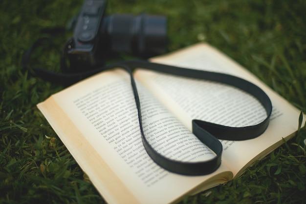 Un libro e una macchina fotografica nel parco, a forma di cuore
