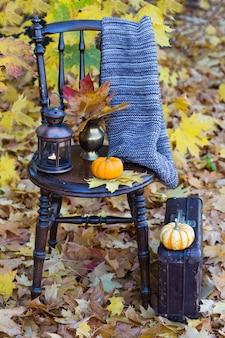 Un libro, una zucca, una sciarpa a maglia, una vecchia lanterna e una vecchia valigia accanto