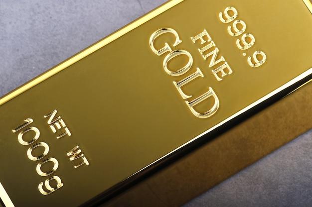 Un lingotto di lingotti d'oro in metallo di puro brillante posto diagonalmente su grigio
