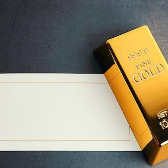 Un lingotto di lingotto metallico dorato che brilla su uno sfondo grigio testurizzato e una carta per scritte. layout, mockup e sfondo per etichette e testo.