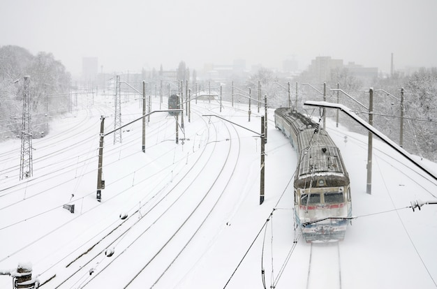 Un lungo treno di autovetture si muove lungo la ferrovia