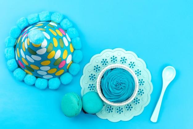 Un macarons francese blu con vista dall'alto insieme a un cucchiaio di plastica bianca da dessert blu e un tappo di compleanno sulla scrivania blu, festa di compleanno
