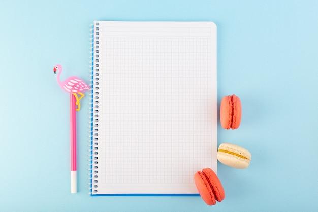 Un macarons francesi di vista superiore con la penna ed il quaderno sulla torta dolce del biscotto dello zucchero da tavola blu