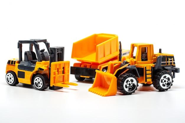 Un macchinario pesante giocattolo giallo include autocarro con cassone ribaltabile, bulldozer e carrello elevatore su bianco