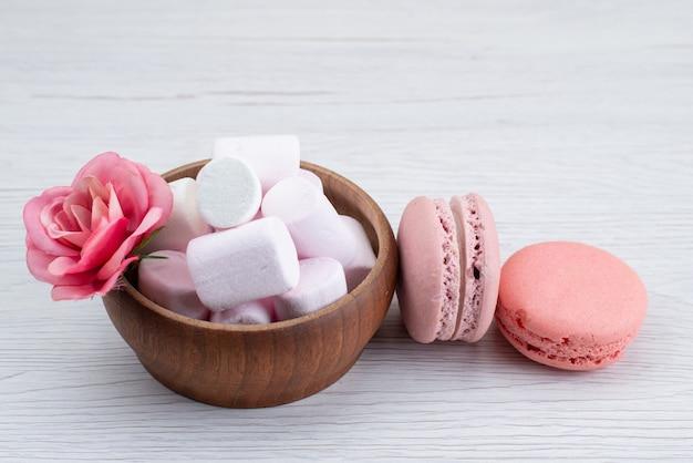 Un marshmallow bianco vista frontale con macarons francesi rosa sullo scrittorio bianco, colore dolce della caramella di zucchero
