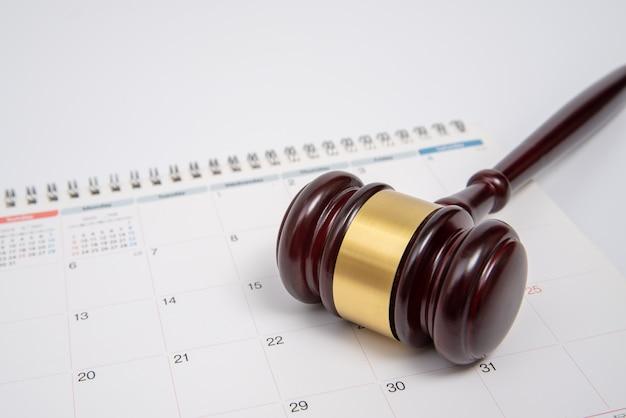 Un martelletto e un calendario di legno del giudice isolati su fondo bianco.