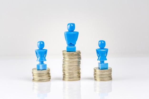 Un maschio e due figurine femminili in piedi su pile di monete.