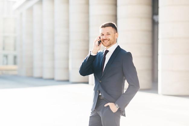 Un maschio soddisfatto con un aspetto positivo risolve i problemi bancari mentre chiama l'operatore tramite smartphone