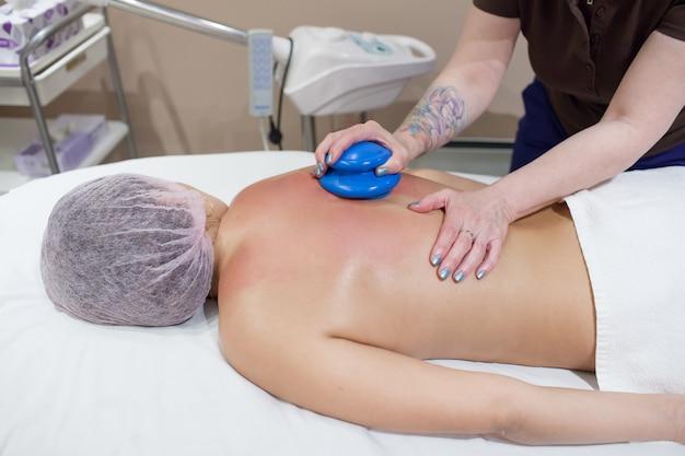 Un massaggiatore femminile che fa il massaggio sotto vuoto.