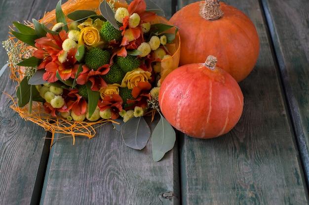 Un mazzo autunnale di fiori autunnali e rose nei toni del giallo e dell'arancio e due zucche