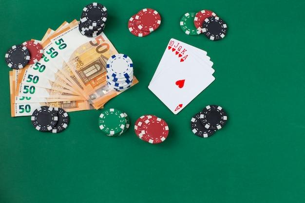 Un mazzo di carte a forma di ventaglio, banconote in euro e carte da gioco