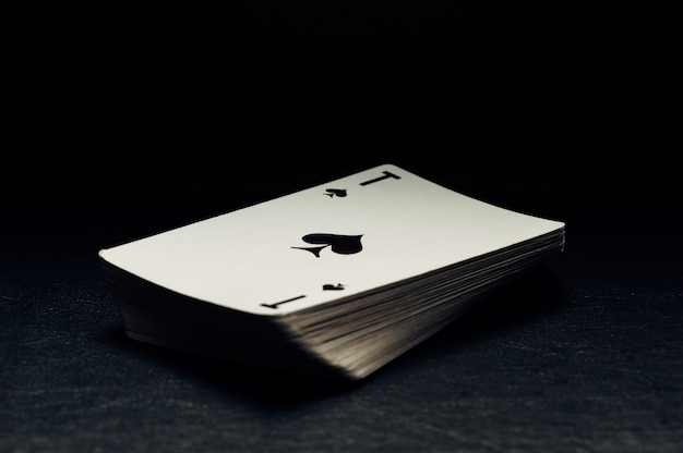 Un mazzo di carte su uno sfondo nero. l'ace di picche.