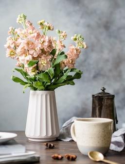 Un mazzo di fiori rosa mattiol in un vaso, una caffettiera vintage, una tazza di caffè e spezie su un tavolo di legno marrone.