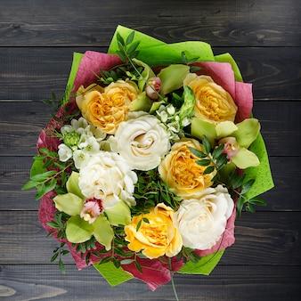 Un mazzo di fiori su un fondo di legno scuro. bouquet con rose.