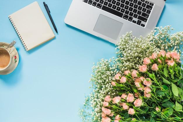 Un mazzo di fiori; tazza di caffè; blocco note a spirale; penna e laptop su sfondo blu