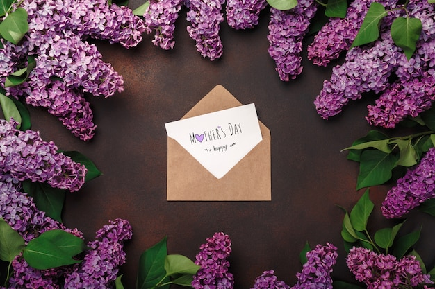 Un mazzo di lillà con busta artigianale, una nota d'amore su sfondo arrugginito. festa della mamma