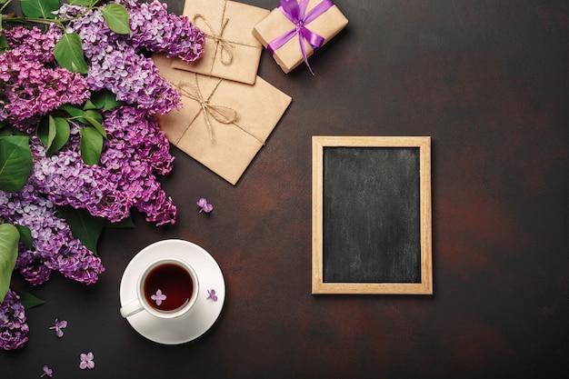 Un mazzo di lillà con una tazza di tè, lavagna, scatola regalo, busta artigianale, una nota d'amore su sfondo arrugginito. festa della mamma