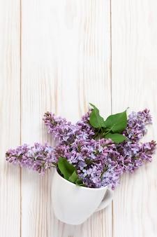 Un mazzo di lillà fragrante fresco in una tazza di porcellana bianca su un fondo di legno bianco.