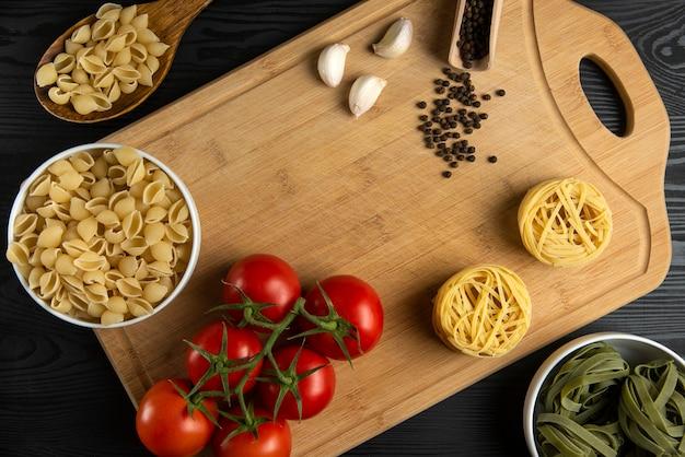 Un mazzo di pomodori con pasta italiana intorno