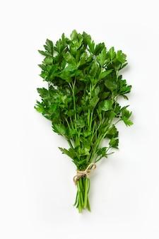 Un mazzo di prezzemolo isolato. prezzemolo verde fresco ed ecologico legato da una corda ecologica.