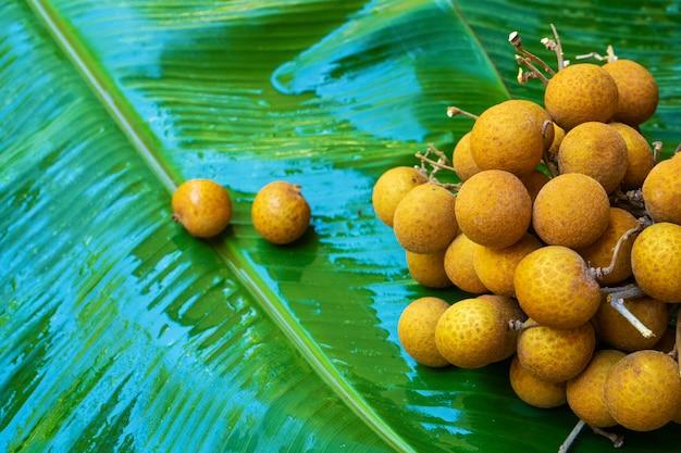 Un mazzo di rami del longan sulla foglia verde della banana. vitamine, frutta, cibi sani