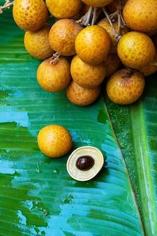 Un mazzo di rami di longan su uno sfondo di foglia di banana verde. vitamine, frutta, cibi sani