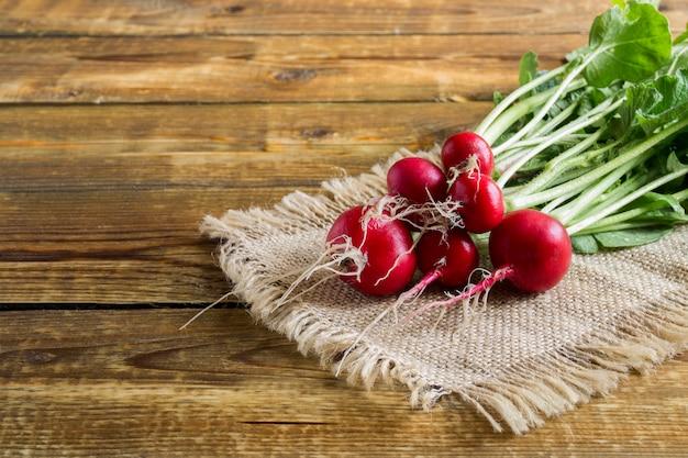 Un mazzo di ravanelli rossi maturi su un fondo di legno