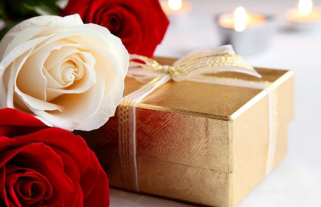 Un mazzo di rose e un regalo su uno sfondo di candele accese. san valentino.