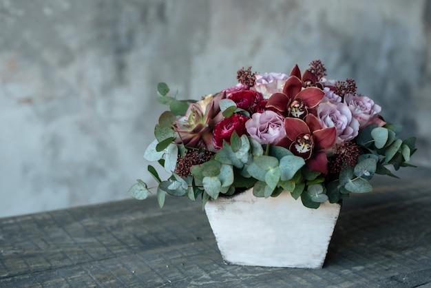 Un mazzo di rose in un vaso di legno è sul tavolo. composizione floreale in un vaso di fiori in legno