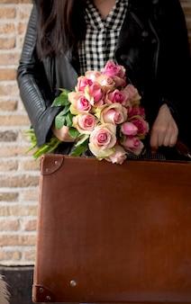Un mazzo di rose nelle mani di una donna con una valigia vicino a un muro di mattoni