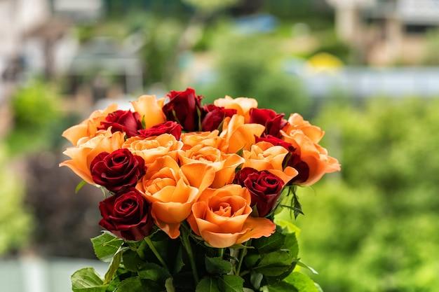 Un mazzo di rose rosse e corallo sul davanzale, luce del giorno, sfondo sfocato.