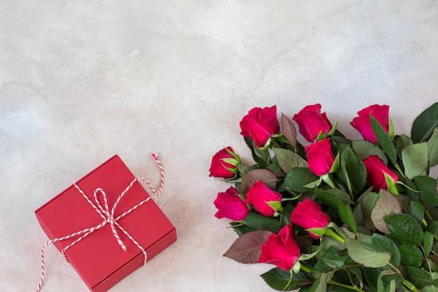 Un mazzo di rose rosse e una confezione regalo rossa