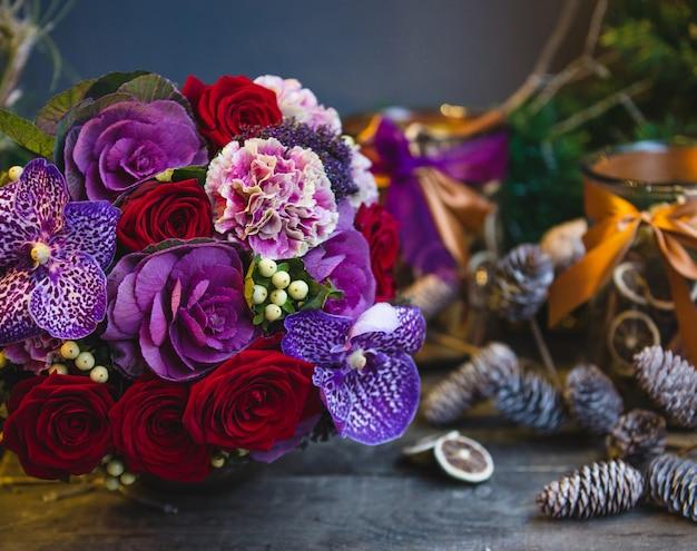 Un mazzo di rose rosse, fiori rosa e viola con foglie sul tavolo di natale