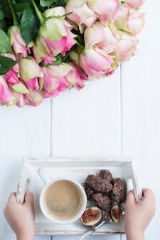 Un mazzo di rose su uno sfondo bianco e una tazza di caffè con cioccolato nelle mani di una ragazza