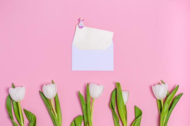Un mazzo di tulipani bianchi, una busta con un lenzuolo bianco e una molletta decorativa su uno sfondo rosa